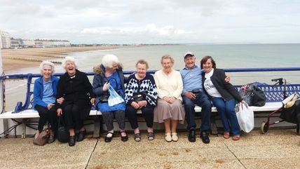 Group from Alfriston sitting on the pier laughing, enjoying the day