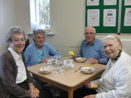 Smiling people being served a cup of tea at the Day Centre